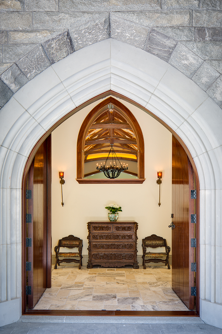 View through main entrance of a Scottish style manor house. Heavy oak doors, stone floors and a peak in to the living room with an orante wood ceiling.