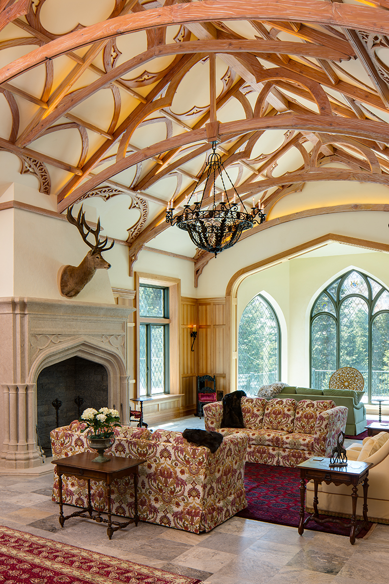 Living room of a replica of a Scottish Style manor house with high vaulted ceilings and elaborate wood truss work. The room also features floor to ceiling leaded, glass windows, a large hearth and taxidermy on the walls.
