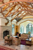 Living room of a replica of a Scottish Style manor house with high vaulted ceilings and elaborate wood truss work. The room also features floor to ceiling leaded, glass windows, a large hearth and taxidermy on the walls.Architectural Photography by: Paul Richer / RICHER IMAGES