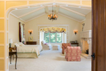Master bedroom in a Scottish manor house with vaulted ceilings and a a large stone hearth and mantle.