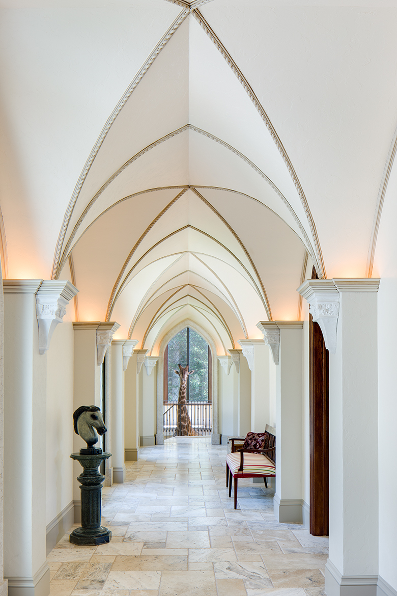 View down long hallway with vaulted ceilings and up lighting in Scottish style manor house with taxidermy Giraffe at end of hall.