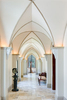 View down long hallway with vaulted ceilings and up lighting in Scottish style manor house with taxidermy Giraffe at end of hall.Architectural Photography by: Paul Richer / RICHER IMAGES