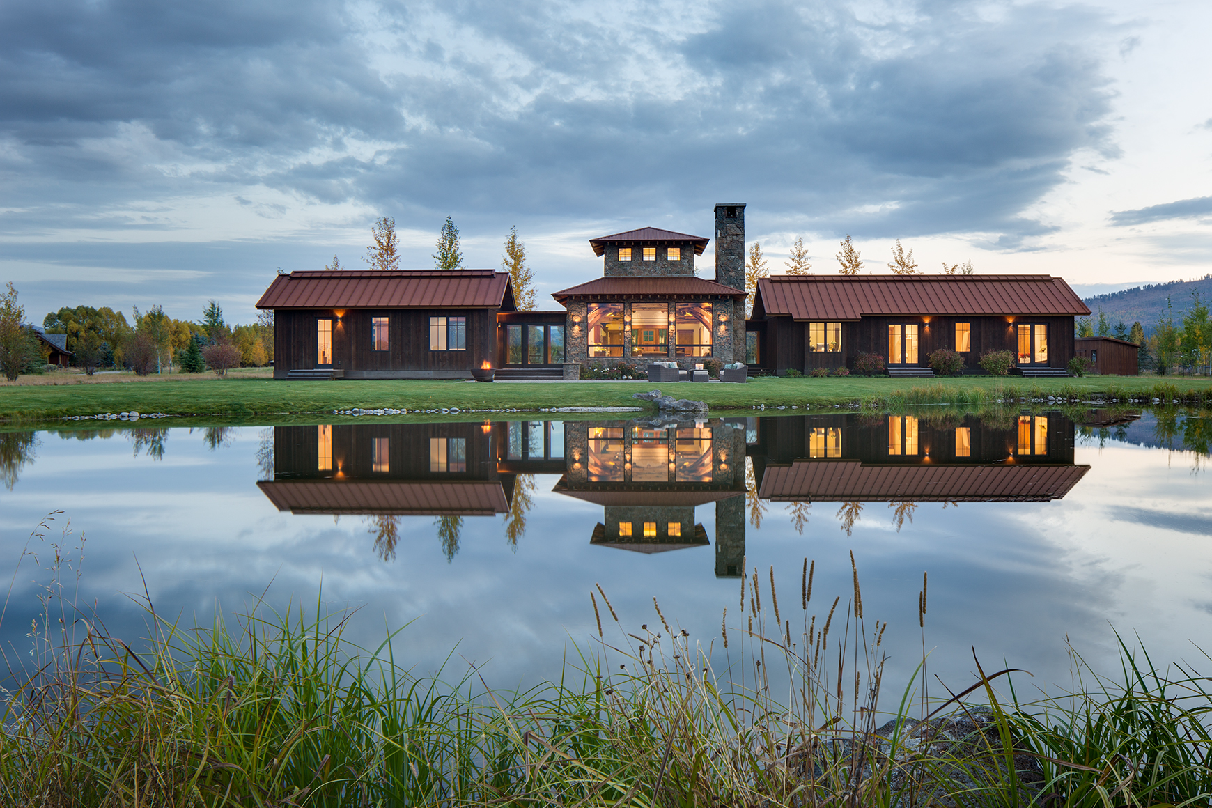 One level contemporary home siting on the edge of a pond at dusk with mirrored reflections.