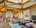 Interior view of main living area with kitchen, living room, fire place and dining room in private residence in Jackson, WY. The architectural high light is the exposed truss work of reclaimed timber.