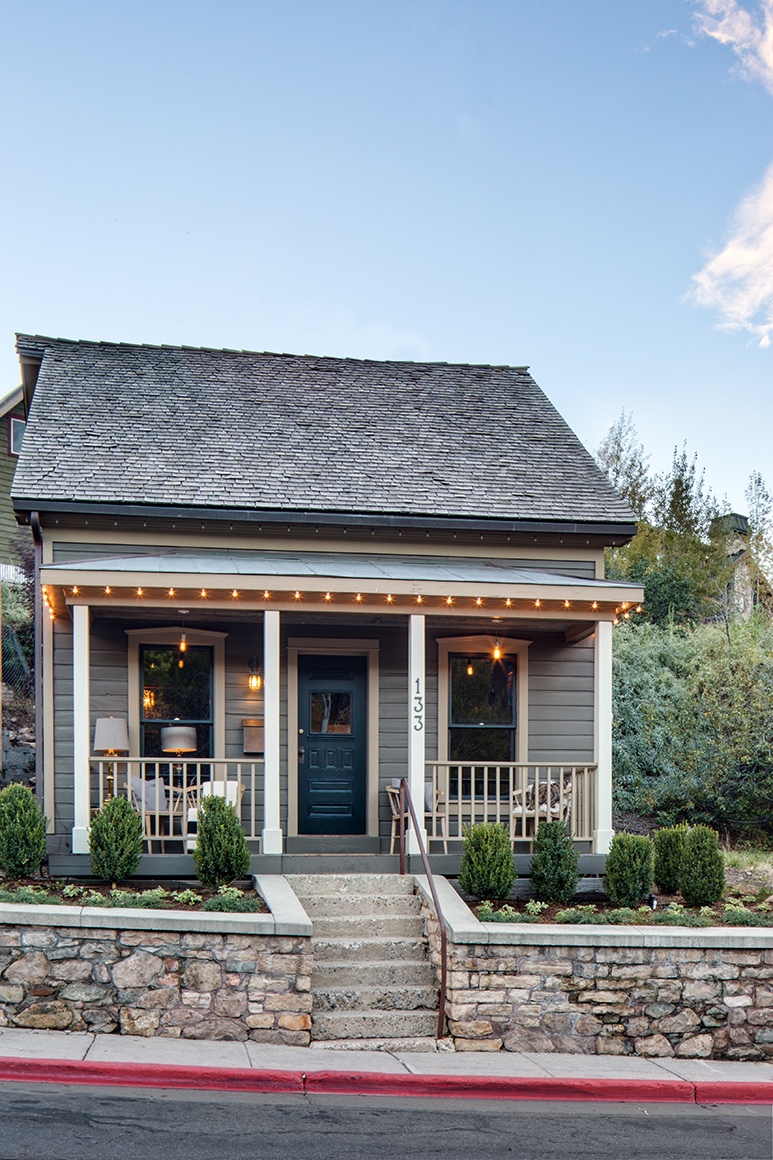 Renovated miners cottage at dusk on Main Street in Park City, UT. with clapboard siding and ornamental lighting.