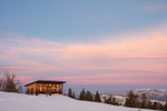 Modern home set high on top of a mountain surrounded by trees and a snow covered meadow. The photograph was taken at dusk so the clouds are oink, the skies are blue and a warm glow is radiating from the windows.