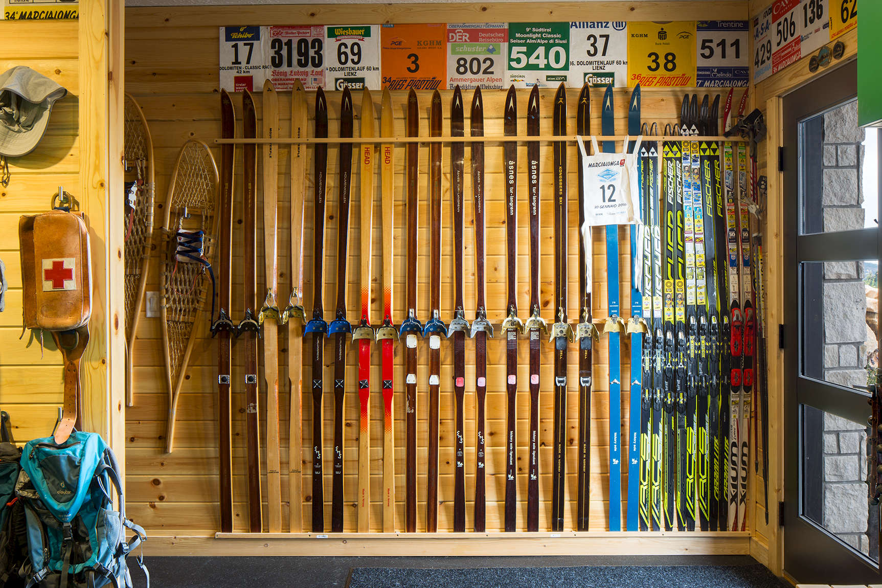 This is an interiord detail photo of a man cave high in the mountains above Park City.The owner of the home is a Nordic Skiing enthusiast and the photograph is of a rack of Nordic skis against an exposed wood in wall illuminated by daylight coming in from the front door.