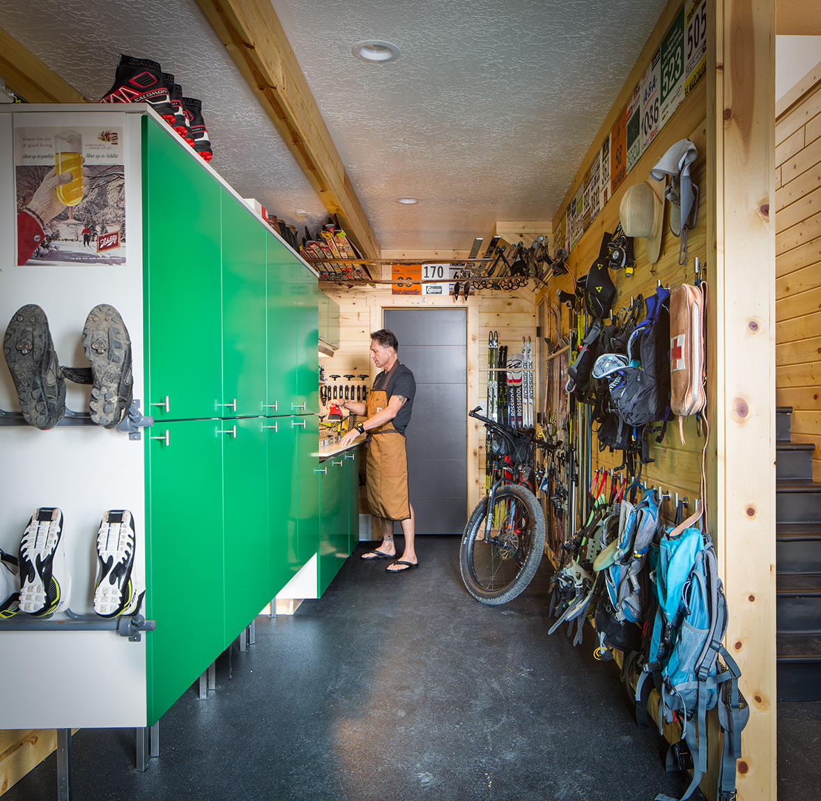 This is a photograph of a man working on his outdoor toys in his man cave at his workbench. The camera is looking down the narrow, room and on one side of the room all of the back pack are hung and on the other side of the room is his work bemch and strorage cabinets with green doors. There are also a few rows of cross country ski boots on the wall facing the camera