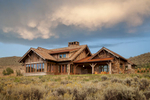This is an exterior view of a rustic home with reclained timbers amidst the sage brush of Park City, UT. The photo was taken in late afternoon and has very dramatic clouds over head.