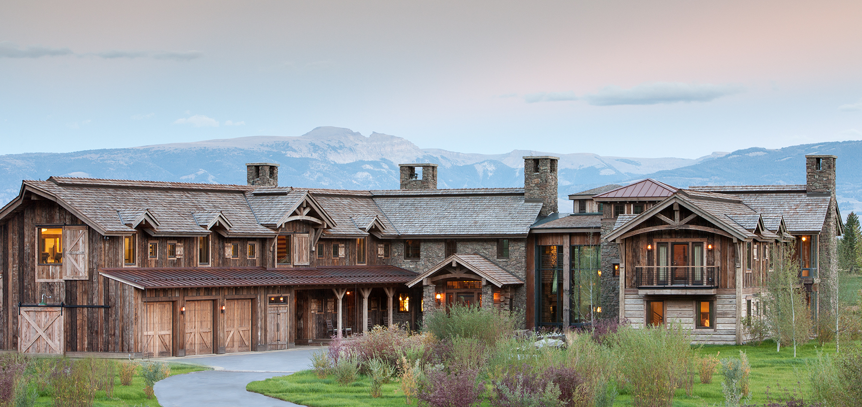 This is an exterior elevation photo of a private residence at Shooting Star in Jackson Wyoming. The house is large and rustic with a raw or reclaimed timber lok to it and has a view of Jackson's Sleeping Indian behind.