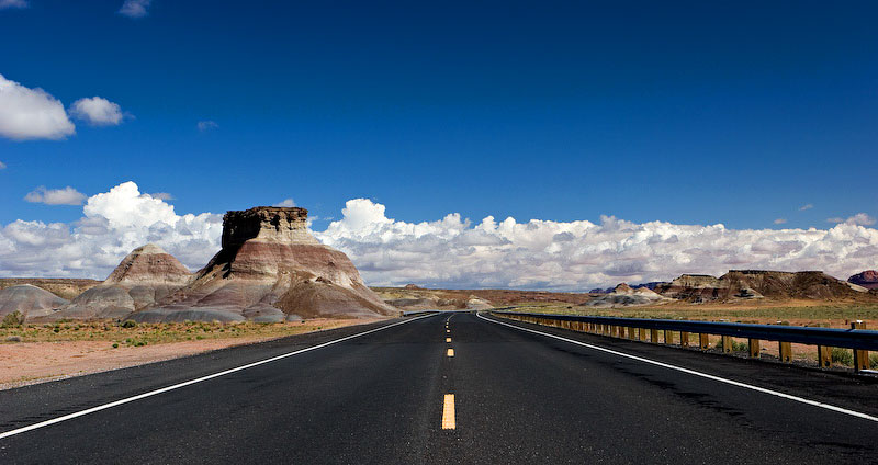 A long stretch of highway extends into a deep blue sky in the vast, open landscape of Arizona.