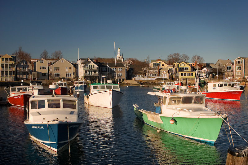 The great colors of these fishing boats, set nicely in a small harbor in Rockport, MA, give one a small taste of New England life by the shore.