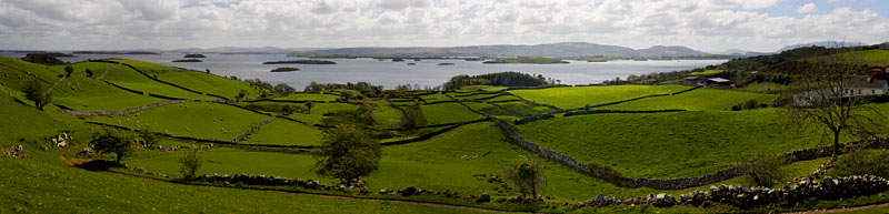 County Mayo, IrelandAncient stone walls divide this lush, green expanse of pasture overlooking Lough Corrib, in Western Ireland. The mild weather nurtures the rich fields on which the sheep graze while a gentle breeze sweeps across the landscape, carrying the comforting and familiar scent of burning peat, heating a nearby cottage.