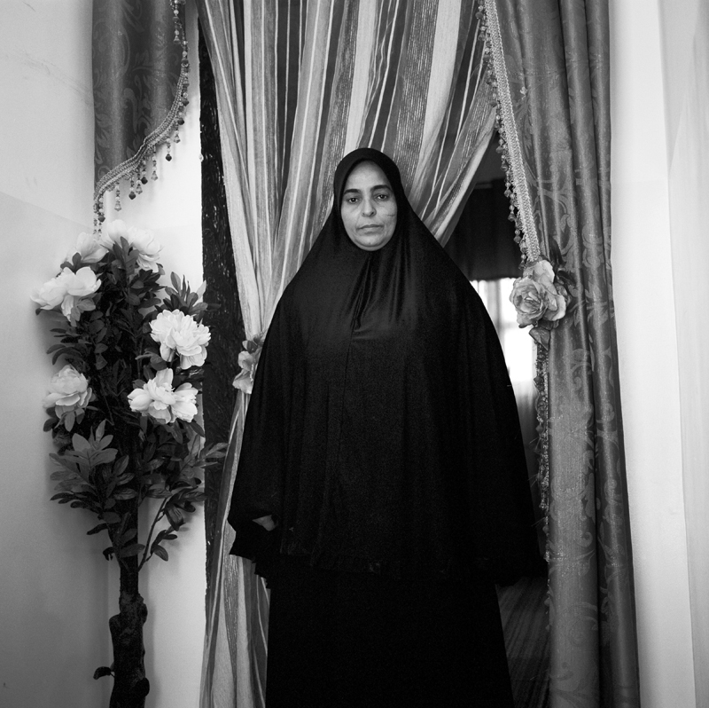 "Zohra El Yakoubi, 48, was married on January 24th, 1989, three months before her husband was taken. ""I think he was arrested because he was religious and people were campaigning against the beard and short pants that prophet Mohamed wore. We kept hearing stories of men being ""picked up"" and he was harassed at the mosque by security officers. My husband used to work at a factory that made flour; he was an electric engineer. Someone at the factory told me that men with guns came one day and took him. A friend of ours tried to break him loose but it wasn't possible for him to help. So many men were taken during this time. For two years we didn't know anything. I started joining protests where we were beaten with sticks. One day Abdullah Senussi read off a list of men in prison and he was on the list. He told us we could go visit our husbands, sons and brothers but we never saw them. My husband learned karate abroad and when men were released from prison they told me that my husband was teaching men karate in prison. I had a son and wasn't able to work; many people helped me out during that time. I had to stay with my mother in law. I used to live very close to Abu Salim prison and we heard everything that happened that night; explosions, ambulances and gunshots. Everyone in the area knew something had happened. We felt in our hearts that night that they had killed him. We lived through some very morbid times. After that night friends and relatives came by, almost to pay their respect. I never saw my husband once and never spoke to him again. In 2007 the regime started pressuring me to take reimbursement money. For men who were married, their wives received 130,000 Libyan dinars and for single men, their parents received 120,000 Libyan dinars. We received his death certificate in 2008 because we kept demanding to know what happened. I always had doubts but this was confirmation of his death and it was still a shock. I didn't get remarried; I wanted to stay single for my son. These were the cards that I was dealt and I have accepted them. The day that Gaddafi was killed I felt a huge weight lifted off of me. I was not stingy with the revolution; I gave it my most precious possession, my son."" Zohra stands at the enterance to her home in Tripoli, Libya on July 23rd, 2012."