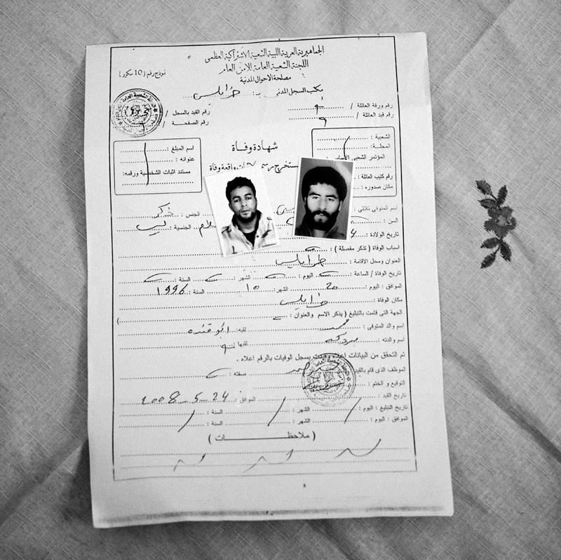 "Zohra El Yakoubi, 48, was married on January 24th, 1989, three months before her husband was taken. ""I think he was arrested because he was religious and people were campaigning against the beard and short pants that prophet Mohamed wore. We kept hearing stories of men being ""picked up"" and he was harassed at the mosque by security officers. My husband used to work at a factory that made flour; he was an electric engineer. Someone at the factory told me that men with guns came one day and took him. A friend of ours tried to break him loose but it wasn't possible for him to help. So many men were taken during this time. For two years we didn't know anything. I started joining protests where we were beaten with sticks. One day Abdullah Senussi read off a list of men in prison and he was on the list. He told us we could go visit our husbands, sons and brothers but we never saw them. My husband learned karate abroad and when men were released from prison they told me that my husband was teaching men karate in prison. I had a son and wasn't able to work; many people helped me out during that time. I had to stay with my mother in law. I used to live very close to Abu Salim prison and we heard everything that happened that night; explosions, ambulances and gunshots. Everyone in the area knew something had happened. We felt in our hearts that night that they had killed him. We lived through some very morbid times. After that night friends and relatives came by, almost to pay their respect. I never saw my husband once and never spoke to him again. In 2007 the regime started pressuring me to take reimbursement money. For men who were married, their wives received 130,000 Libyan dinars and for single men, their parents received 120,000 Libyan dinars. We received his death certificate in 2008 because we kept demanding to know what happened. I always had doubts but this was confirmation of his death and it was still a shock. I didn't get remarried; I wanted to stay single for my son. These were the cards that I was dealt and I have accepted them. The day that Gaddafi was killed I felt a huge weight lifted off of me. I was not stingy with the revolution; I gave it my most precious possession, my son."" Zohra's husbands death certificate accompanied by photos of her son (right) and husband (left) at her house in Tripoli, Libya on July 23rd, 2012."