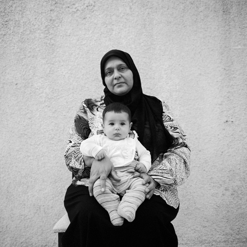 "Wedad Ftieta, 52, was married in July of 1983. ""I was three months pregnant when he was captured. We are from Benghazi. My husband was born in 1955 and went to England to study electronic engineering. When he was in England he joined a students union against Gaddafi. It was secret and the government didn't know about it so he was still able to return to Libya. He came back in April 18th, 1986. Twenty days later, he was captured. After they captured him, I didn't know where he was until 1988. That year I was able to visit him. I found out he was in the prison by word of mouth. On my first visit, I brought our son. I tried to see him once a month. When I went to visit him, they humiliated us. They would throw my food on the ground and watch me collect the pieces. I was given 10 minutes per visit. There were signs of torture on his body, but he never said anything about it. I heard they would leave men alone in a room with a wild dog to attack them. He lost a lot of weight, I felt huge around him. My last visit with him was in May of 1996, less than a month before the massacre.  He told me the prison was spooky and gray and that there was something going on.  The visits were stopped after the massacre. I heard there was shooting, but no one knew anything. In 2000, his case was taken to court. There were five other men who he was being tried with. The five men were present, but he was not there. The five men, and Ahmed were given life sentences. After 2000, we were allowed to visit again, but I never got to see him. The guards started to give me letters from him, that he needed money, clothes, food and medicine. In the letters he asked how the family was and wrote that I could write freely to him. All the women could visit their husbands, but I couldn't. In 2002 the men who he was tried with were released. They told me that they hadn't seen him since 1996.  In 2009 prison guards told me that he was going to be freed. During that time, I was preparing for my sons wedding. We pushed it back to wait for his release. I was always waiting for him, and thought he'd be released one day.  I was waiting, dying for Tripoli to be released. But it was very sad for me when all the prisoners where released from Abu Salim prison. Only after Tripoli fell did I know that he was really dead. I can't believe I have been waiting for my husband who died in 1996. I've lived in hope for such a long time. Ahmed died a martyr for this revolution."" On April 4th, 2012 in Tripoli, Libya, Wedad hold's her grandson Ahmed, named after her husband who was killed in Abu Salim."