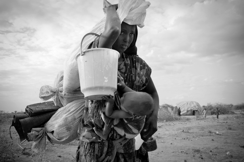 A Somali Refugee at Ifo extension carries her belongings, as well as her child. As many as 1,500 refugees are arriving daily. Although designed to hold only 90,000 refugees, over 400,000 people have streamed in.
