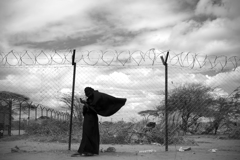 A new Somali arrival uses her cell phone outside the reception center in Dadaab refugee camp.