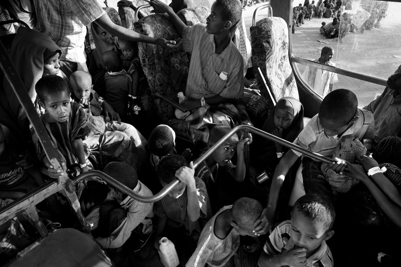 New Somali arrivals are loaded onto a bus at the reception center and driven to the registration center where they are photographed and Id's. The buses are packed with new arrivals, children are seated on the dashboard of the bus and on the floor.
