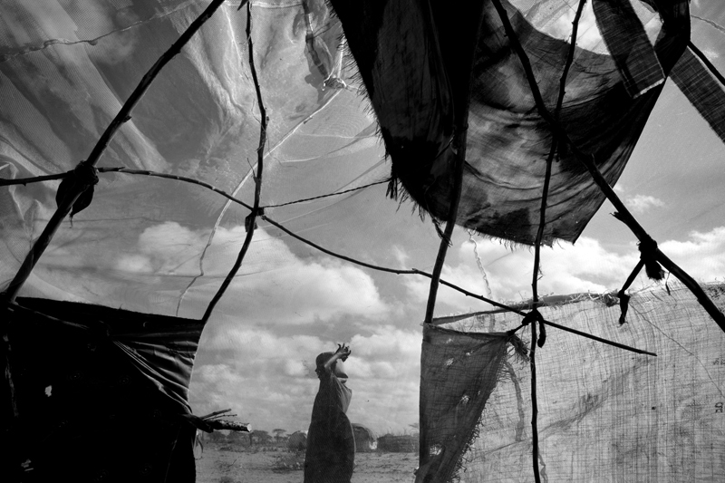 A crude shelter made of sticks, torn cloth and a mosquito net sits on the edge of Ifo Extension within Dadaab Refugee Camp.