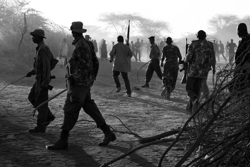 Kenyan police officers defend the compound of a food distribution by beating Somali refugees with sticks, rubber hoses and firing shots into the air to disperse the crowd.