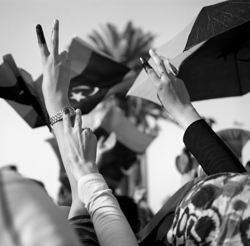 Women celebrate in Martyrs Square, waving their inked fingers in the air after voting in Libya's historical Parliamentary election