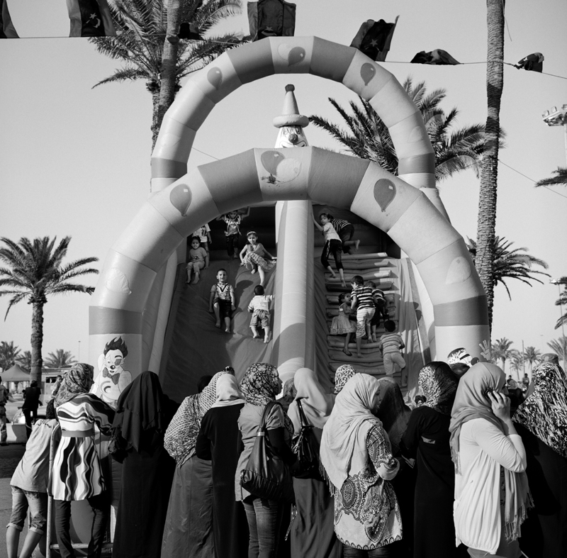 Women in Martyrs Square watch their children on the bouncy castle in Tripoli, Libya