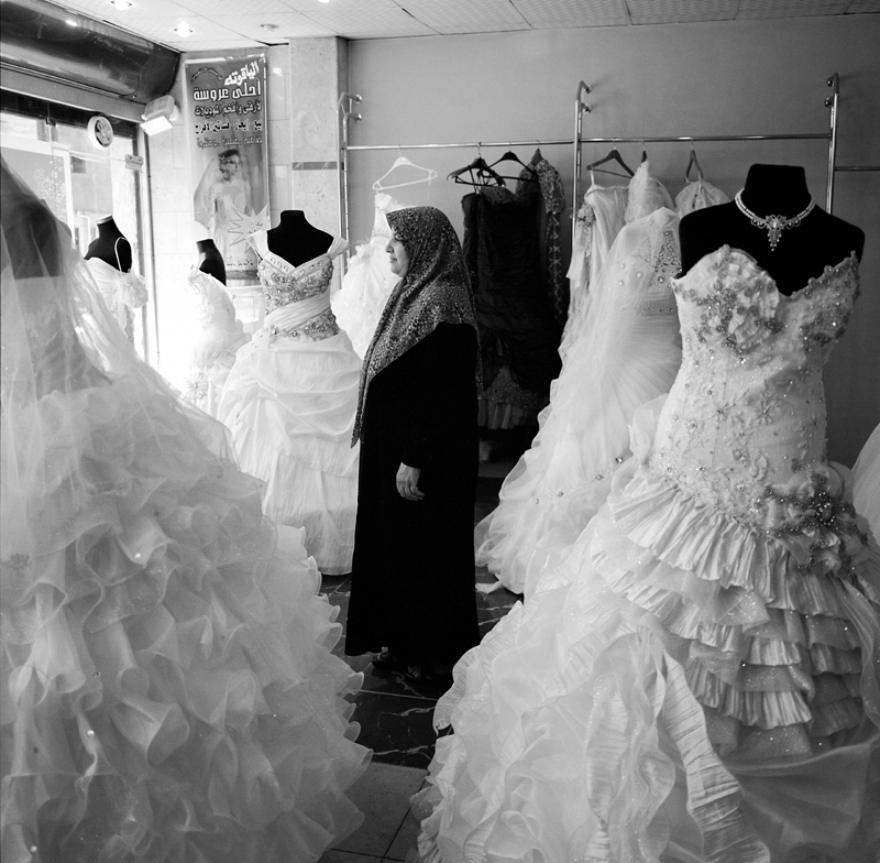 Weded Elbede, 52, stand in the bridal store that she has owned for the past six years. She has supported the revolution from the beginning, and all five of her sons fought to liberate Tripoli. After the revolution began in February, men working for Muammar Gaddafi would stop by her store, threatening to keep it open or else they would take it from her. {quote}They wanted things to look normal,{quote} she explains. In April she closed her store {quote}I grew tired of what was happening in the country and I wanted to show the world everything was not ok. I kept the shop closed until Tripoli was liberated.{quote} They opened the store again on the last day of Ramadan to show that things were going back to normal. One night during the revolution men supporting the rebels created a roadblock in front of her store, and raised the national flag. A father and son supporting Gaddafi lowered the flag and burned it, then called troops loyal to the repressive leader. {quote}African's showed up wearing green flags on their head, there was heavy machine gun fire. I live above my store, and many bullets broke the windows in my house.{quote} On August 23rd her youngest son was fixing his bike outside her store when a man in a taxi drove by spraying the street with bullets. He was shot four times in the back, along with other children who were playing outside. {quote}A lot of taxi's were involved in drive by shootings as many were secretly working for internal intelligence. Leading up to the revolution I heard some taxis were working for free so they could speak to more people and gather information, they were targeting the youth.{quote}