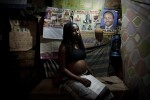 "KIBERA SLUM – JULY 29: A 20 year old Kenyan woman who is 6 months pregnant sits in a midwifes house in the slum of Kibera in Nairobi, Kenya on July 29th, 2010. Her father, the main bread winner in her family passed away 3 years ago. She lives with her mother, 2 brothers and 3 sisters in a one-room shack in Kibera; they can barely afford to pay the rent each month. Her boyfriend abandoned her when he found out that she was 2 months pregnant, she is due October 3rd. Due to lack of family planning in Kenya, many women are left to raise children alone without any means of an income. She says that her culture believes if you abort your first pregnancy then you will become barren and never have children so she plans to keep her baby. ""Feeding my baby will be a problem, it won't eat a balanced diet."""