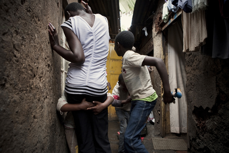 KIBERA SLUM - JULY 11: Children play in the alley way outside their home in the slum of Kibera in Nairobi, Kenya on July, 11th, 2010. Their aunt, a 31-year old single woman takes care of the 9 children. Her brother and his wife died of HIV and her sister died in 2008 after ingesting 25 aspirin to terminate an unwanted pregnancy. Their children now live with her in a single room in Kibera. {quote}It is very difficult to bring up all these kids alone, work is unpredictable, we usually skip lunch and porridge is our main meal in the evening.{quote} On a good month she can make up to 1,500 Kenya shillings, on a bad month she will only earn 900. Her 17-year-old niece who also lives with her is 6 months pregnant. Her boyfriend left her after learning of the pregnancy. She contemplated an unsafe abortion but her aunt and her pastor urged her to keep the child, as an abortion is life-threatening procedure in Kenya.