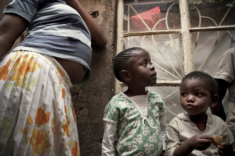 KIBERA SLUM - JULY 11: A 31-year old single woman takes care of 9 children who are her nieces and nephews in the slum of Kibera in Nairobi, Kenya on July, 11th, 2010. Her brother and his wife died of HIV and her sister died in 2008 after ingesting 25 aspirin to terminate an unwanted pregnancy. Their children now live with her in a single room in Kibera. {quote}It is very difficult to bring up all these kids alone, work is unpredictable, we usually skip lunch and porridge is our main meal in the evening.{quote} On a good month she can make up to 1,500 Kenya shillings, on a bad month she will only earn 900. Her 17-year-old niece who also lives with her is 6 months pregnant (pictured). Her boyfriend left her after learning of the pregnancy. She contemplated an unsafe abortion but her aunt and her pastor urged her to keep the child, as an abortion is life-threatening procedure in Kenya.
