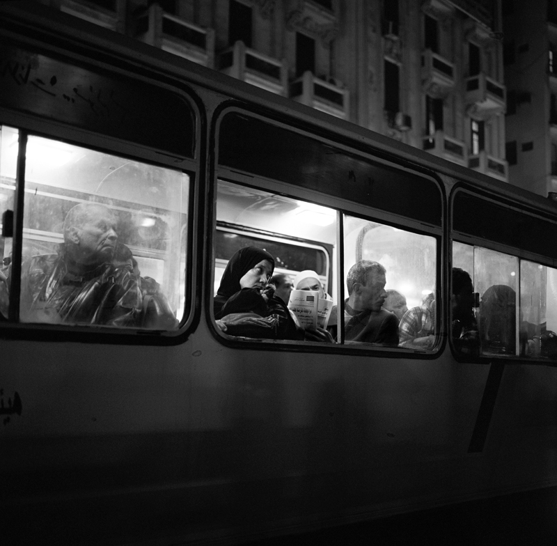 "A woman watches from a bus as a demonstration takes place outside of a courthouse in Cairo. The demonstrators are protesting the continuation of bloodshed and the brutality of the military and police. The phrase {quote}Couch Party"" has been coined in Egypt to describe the silent and often uninvolved majority who sit and watch the protests on TV."