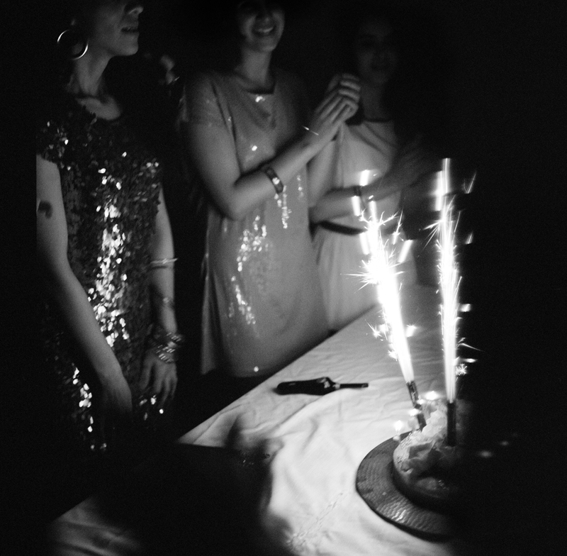 A Libyan girl celebrates her 21st birthday at her parents home in Tripoli. Girls who usually wear a hijab or abaya wear revealing dresses since men are not present. Girls arrive at the house in robes, concealing their party dresses. The girls spend time dancing to Western music and eating sweets before dinner and finally a birthday cake.