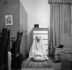 A Libyan woman prays in prayer garments in her bedroom. When Muslims pray they present themselves to God in the act, to be fully covered is a mark of respect. Muslim women are required to dress modestly as required by the Holy Qur'an. Women are not required to wear prayer attire unless their clothes are tight.