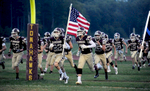 9/15/17-- NORTHBOROUGH--  Algonquin's Zack Smith leads the team onto the field with the American flag Friday night before the game against Marlborough. [Daily News and Wicked Local Staff Photo/Art Illman]
