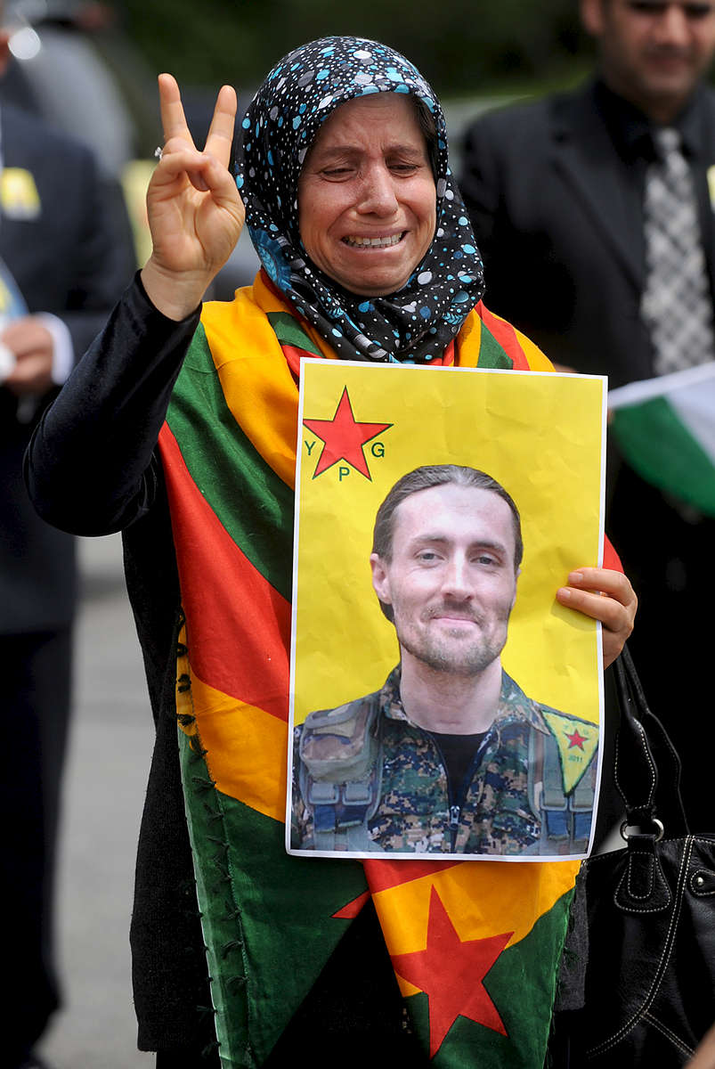 A woman holds a photograph of Keith Broomfield after the funeral for Broomfield at Grace Baptist Church in Hudson.  The local Kurdish American population lined up with flags and photographs behind the church.  They met privately with the Broomfield family. Broomfield was killed in Syria fighting for a Syrian Kurdish militia against the Islamic State.Daily News Staff Photo/Art Illman