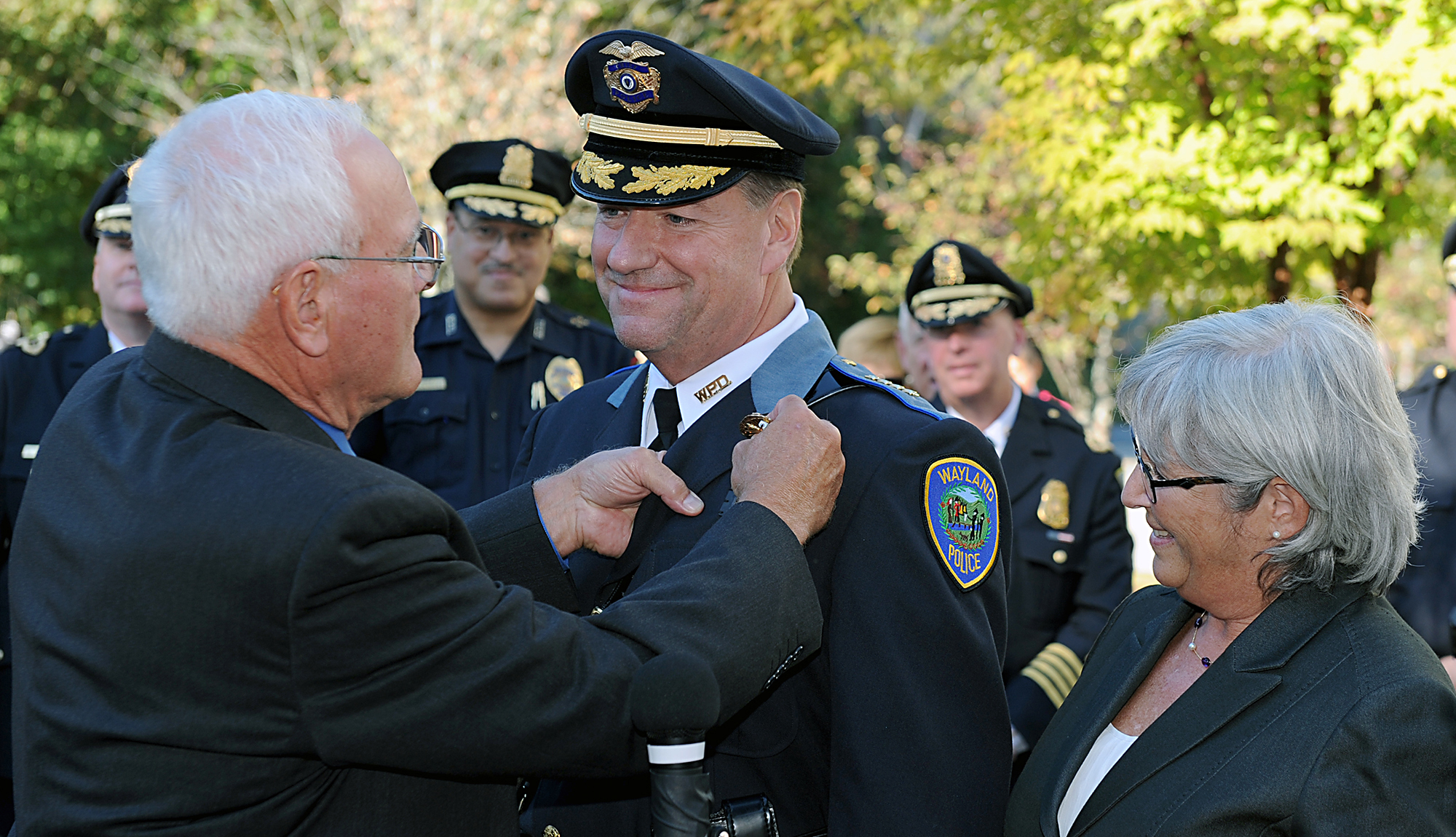 10/2/17-- WAYLAND-- Newly sworn in Wayland Police Chief Patrick J. Swanick has his badge pinned on by retired  Wayland police Sgt. Bob Parker Monday afternoon outside the Wayland Public Safety Building. At right is Swanick's wife, Heidi. [Daily News and Wicked Local Staff Photo/Art Illman]