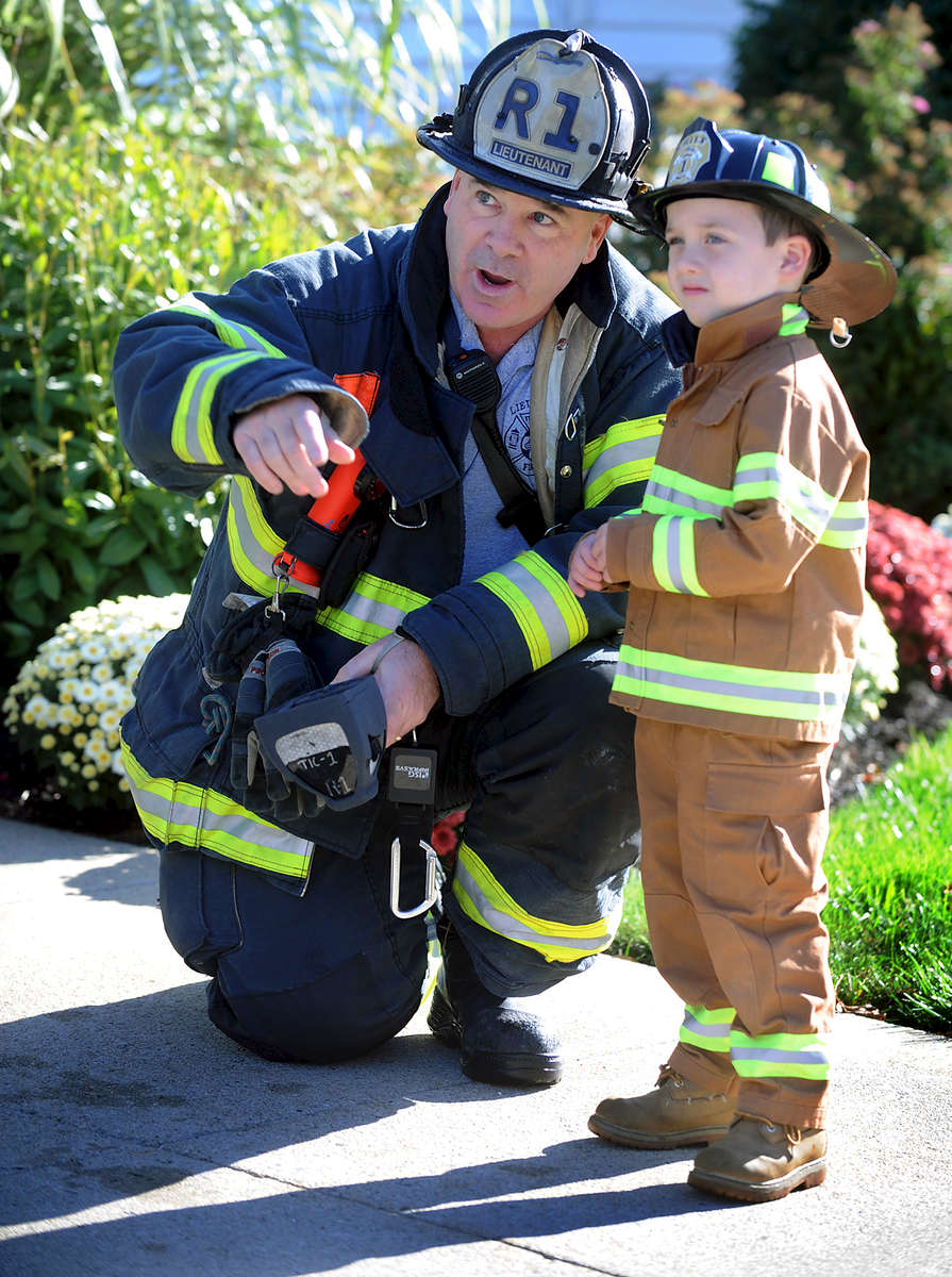 10/12/17-- FRAMINGHAM--Devin McKinney, 4, gets the run down from Framingham Fire Lt. Tom Rinoldo, before firefighters trained at 19 Lincoln St. Thursday morning. The house, which will be demolished in the next few weeks,  was made available for firefighters to train in by McCarthy, McKinney and Lawler Funeral Home.  Devin is funeral director Brian McKinney's son.  {quote}It's his Halloweeen costume but he wears it all the time,{quote} said his mom, Kerrin. {quote}This is a dream come true for him.{quote}  [Daily News and Wicked Local Staff Photo/Art Illman]
