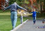 Ben Stillman, 2, of Natick, walks a balance beam of sorts with grandparents Bob and Cathy Wardwell, of Connecticut, at John J. Lane Park.Daily News Staff Photo/Art Illman