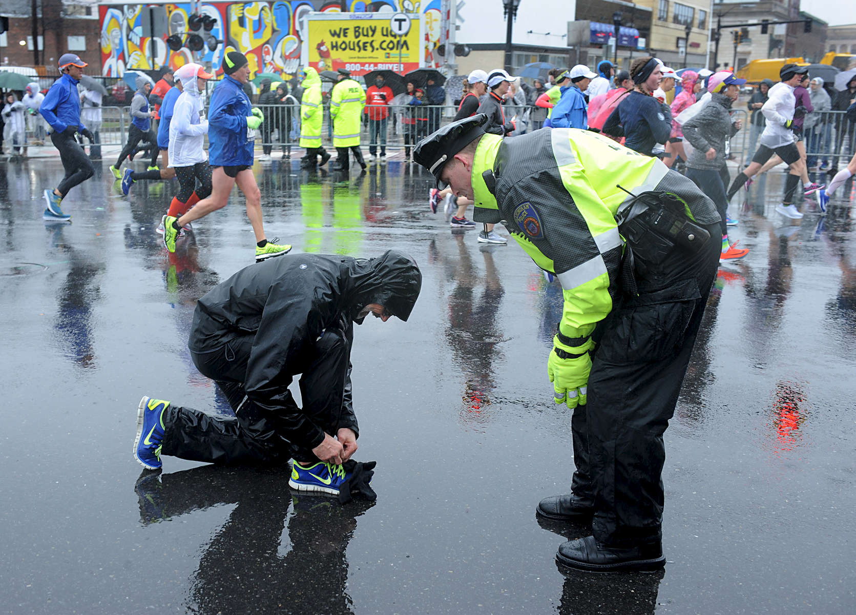 4/16/18-- FRAMINGHAM--   Framingham Police Officer Garrett Coffin checks on a runner at the 2018 Boston Marathon. [Daily News and Wicked Local Staff Photo/Art Illman]