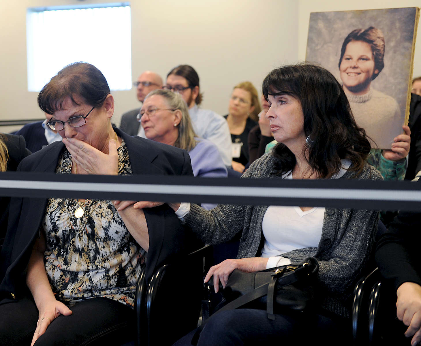 3/29/16 NATICK--   Jeanne Quinn, left, is consoled by family and friends at the Mass. Parole Board hearing Tuesday for Rod Matthews, who murdered Quinn's son, Shaun Ouillette, in Canton in 1986, when both boys were 14 years old. A photo of Shaun was held up by a family member throughout the four hour hearing.Photo by Art Illman/MetroWest Daily News