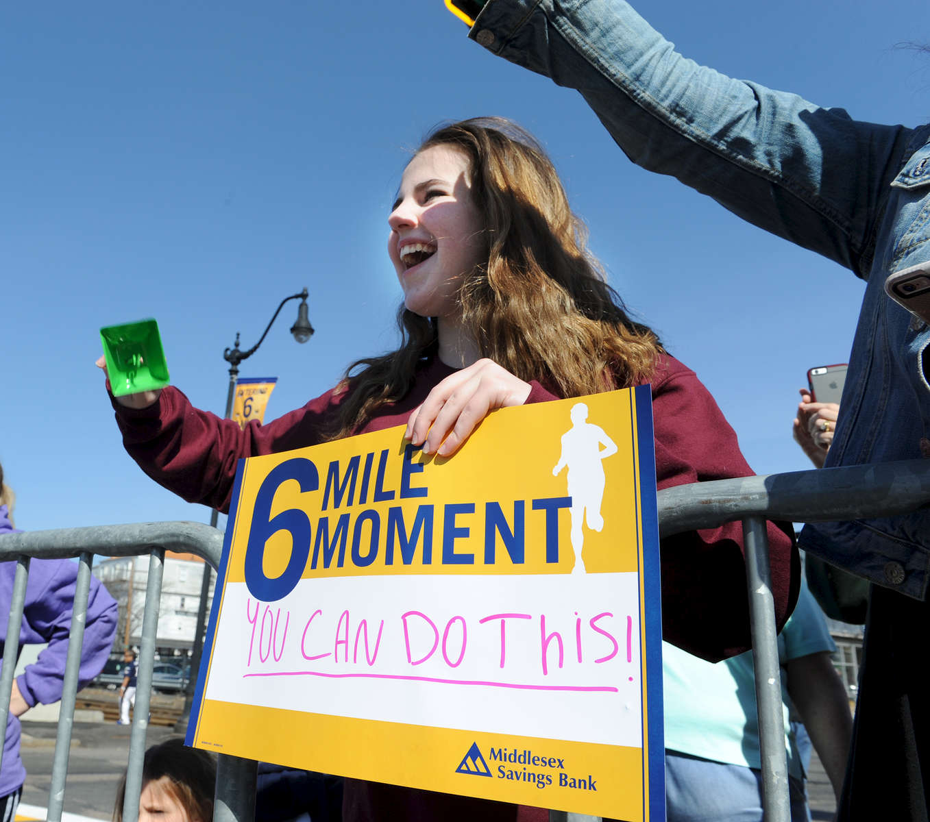 4/18/16-- FRAMINGHAM-- Kyla O'Donnell, 14, of Michigan, cheers in downtown Framingham Marathon Monday.Daily News and Wicked Local Staff Photo/Art Illman