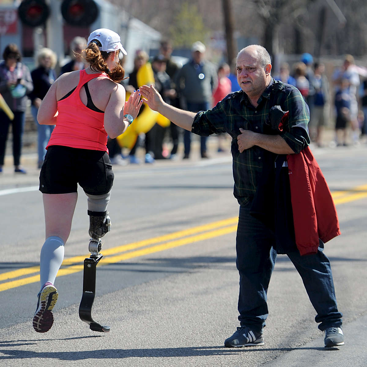 4/18/16-- FRAMINGHAM-- In downtown Framingham on Marathon Monday, Joe Chaves of Hudson high fives Kathryn McCauley.Daily News and Wicked Local Staff Photo/Art Illman