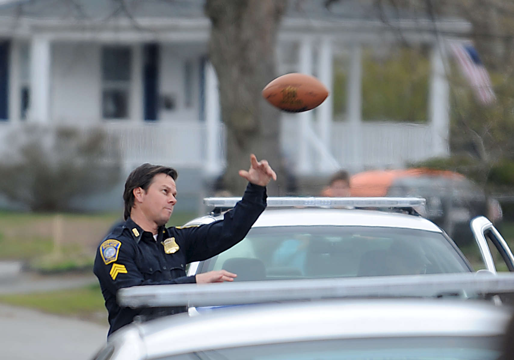 4/19/16-- FRAMINGHAM-- Actor Mark Wahlberg throws a football  during a break while filming the movie Patriot Day on Harrison Street in Framingham Tuesday.  Wahlberg plays Boston Police Sgt. Tommy Saunders in the story of Boston Police Commissioner Ed Davis's actions in the events leading up to the 2013 Boston Marathon bombing and the aftermath, which includes the city-wide manhunt to find the terrorists behind it.Daily News and Wicked Local Staff Photo/Art Illman