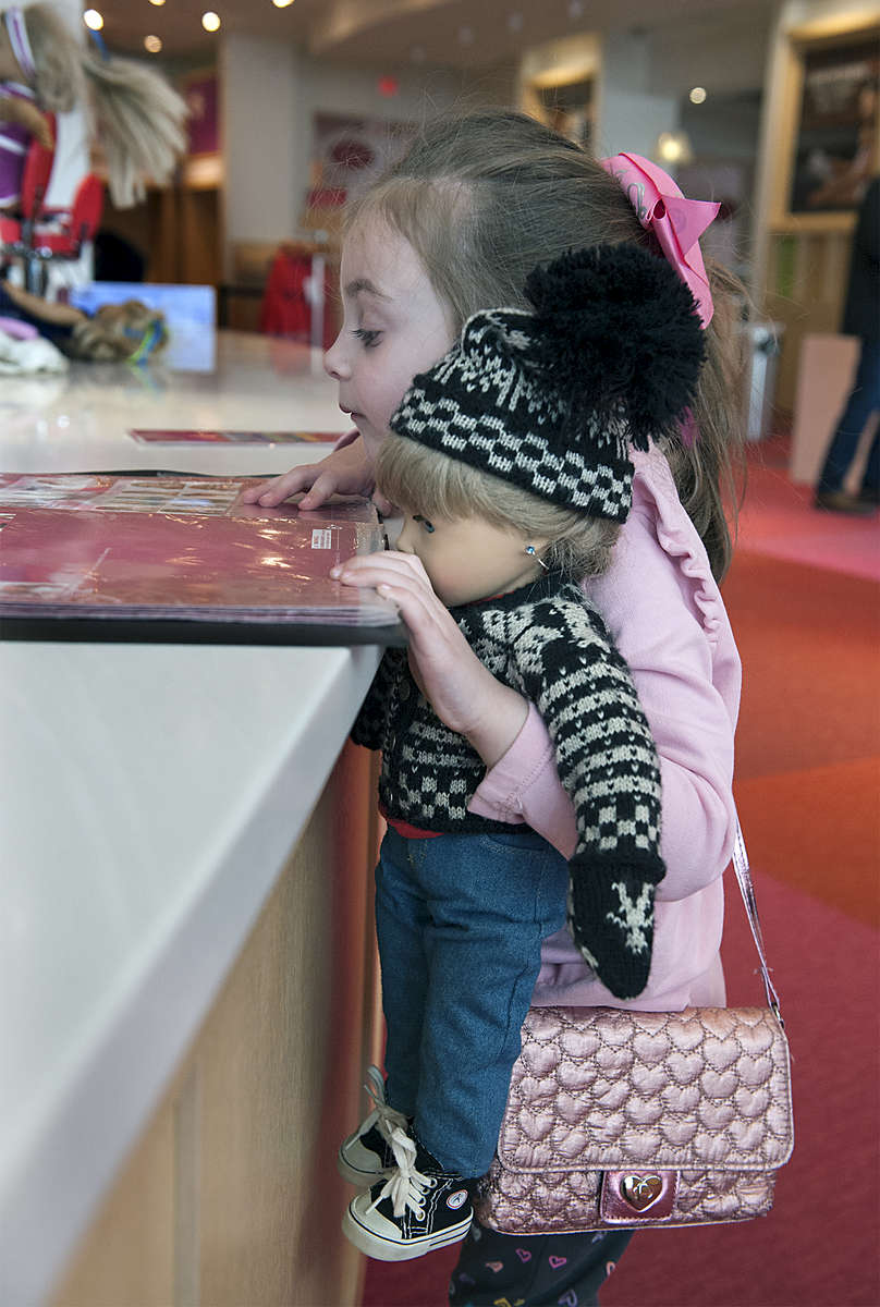 3/20/19-- NATICK-- Grace Rizzo, 4, of Milton,  looks through a catalogue at the American Girl Doll Hair Salon, holding Kiersten, an American Girl doll that belonged to her mom, Karly.  The Natick Mall store closed on Wednesday. [Daily News and Wicked Local Staff Photo/Art Illman]