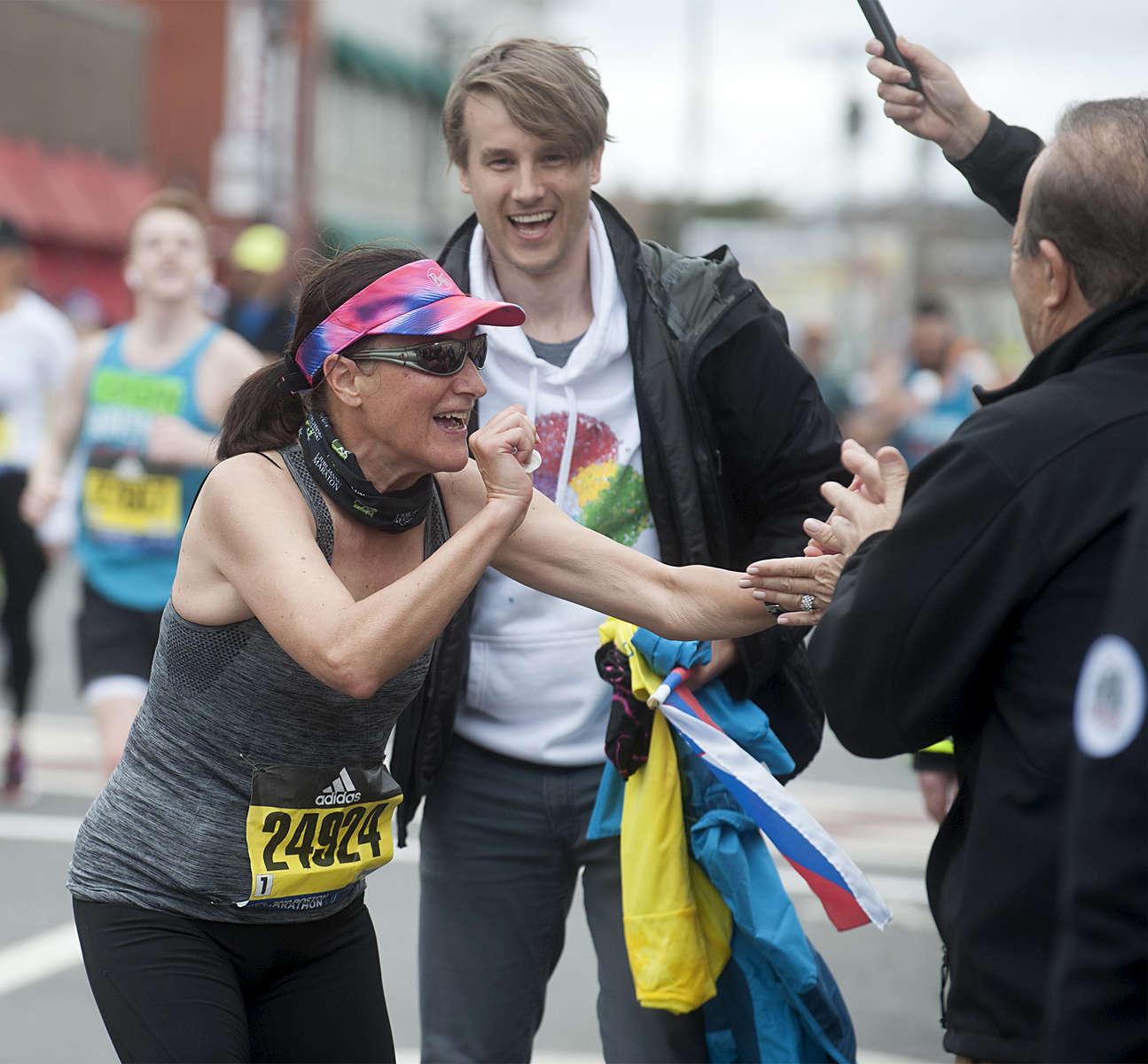 Boston Marathon runner Edna Cibej, of Slovenia, found her family waiting in Framingham: son Vid and husband Jadran. [Daily News and Wicked Local Staff Photo/Art Illman]