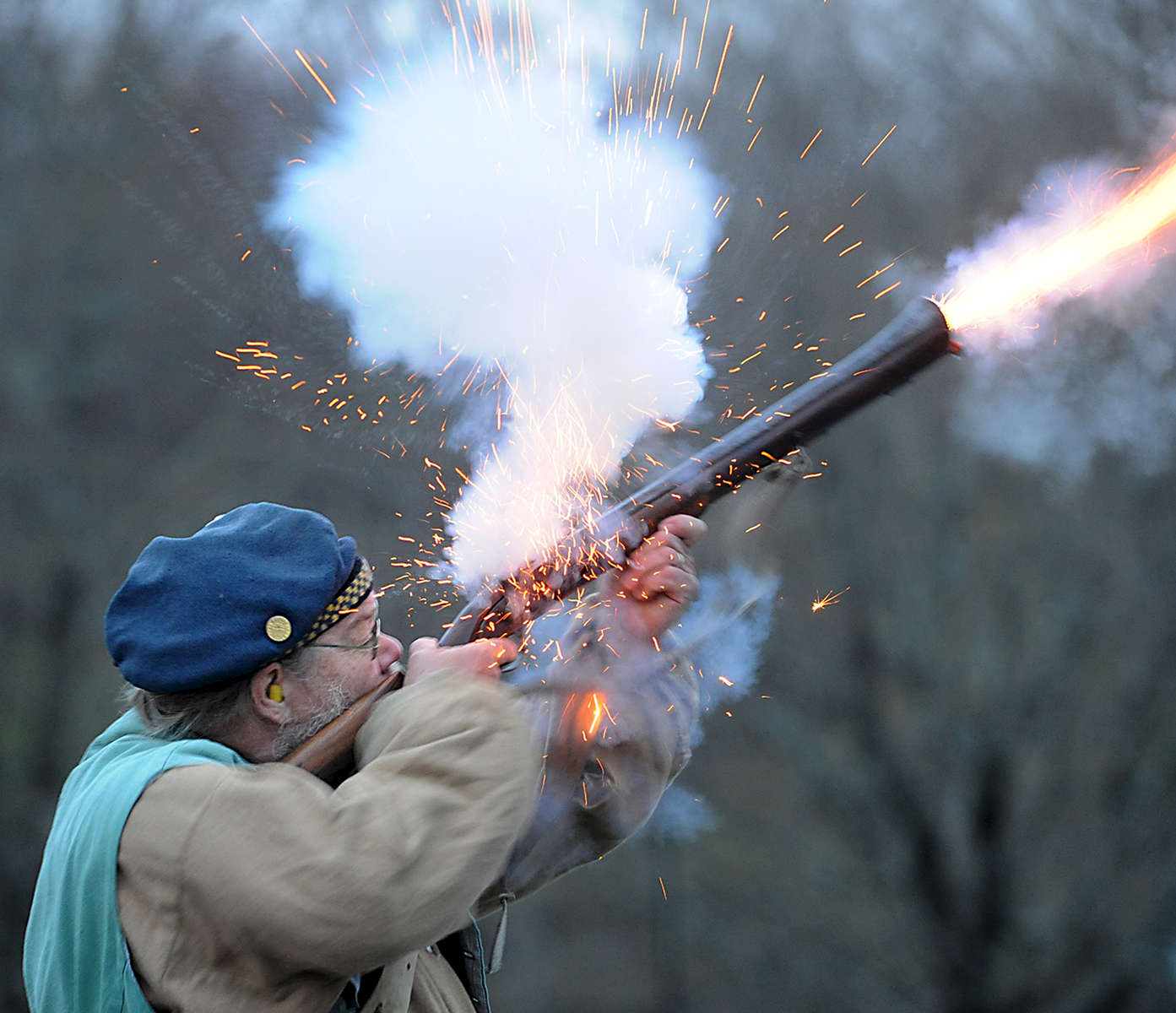 4/19/17-- SUDBURY-- Eric Vollheim, who joined the Sudbury Companies of Militia and Minute in the 1960s as a Boy Scout, fires his musket in front of Sudbury Town Hall, on Patriots' Day, April 19, 2017, the 242nd anniversary of the Battles of Lexington and Concord and the start of the American Revolution. [Daily News and Wicked Local Staff Photo/Art Illman]