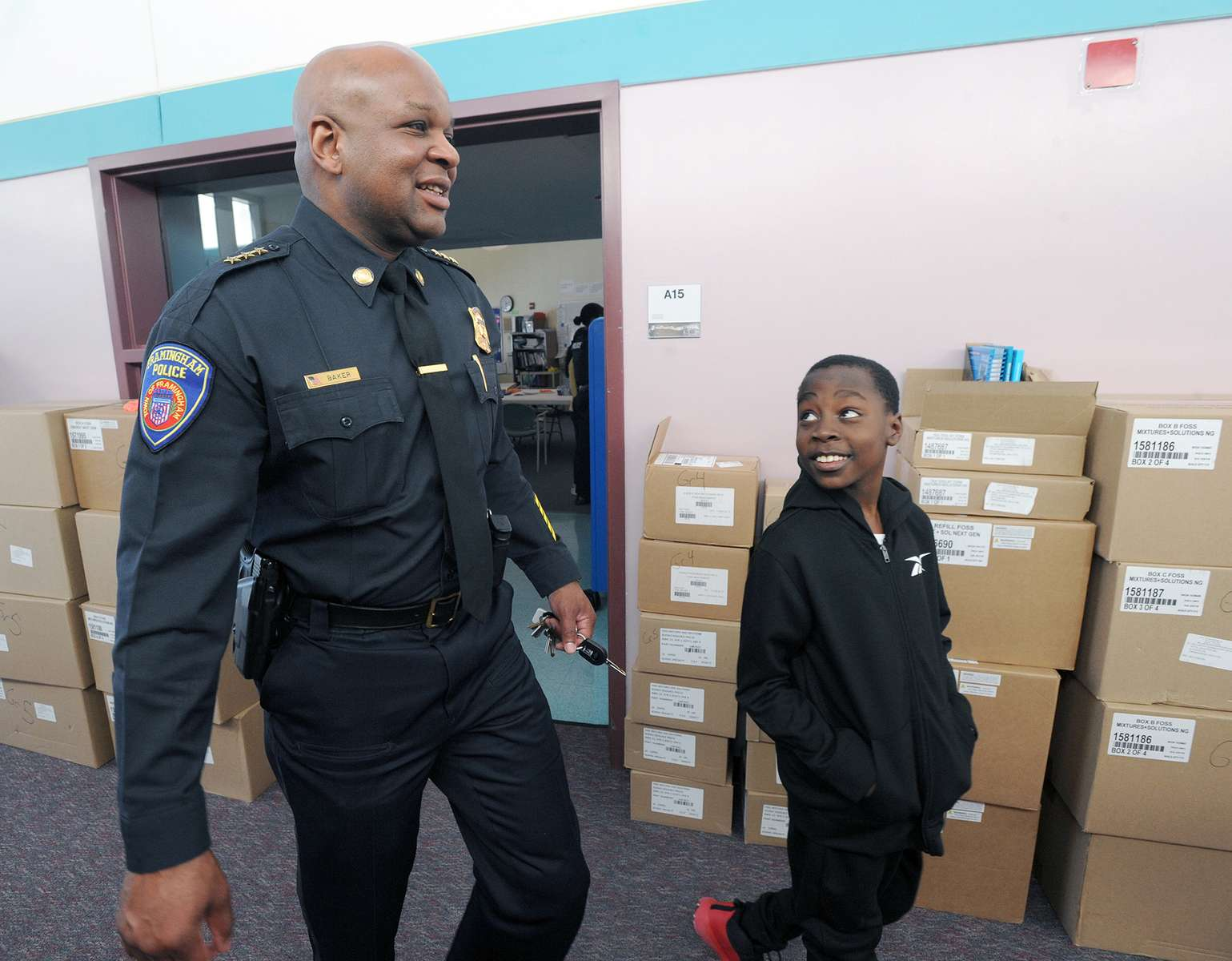 1/22/20-- FRAMINGHAM-- Framingham Police Deputy Chief Lester Baker, here with fifth grader Blessed Tenthani,  was one of five {quote}Bigs in Blue{quote} Big Brothers Big Sisters at the McCarthy Elementary School Wednesday.  The officers ({quote}bigs{quote}) meet with their {quote}littles,{quote}  who all attend the after school program at the MetroWest YMCA,  once a week, for a minimum of one year. So far the students have toured the police station and have other events planned.  Wednesday the students took their Big Brothers Big Sisters on a tour of the school after a pizza lunch. [Daily News and Wicked Local Staff Photo/Art Illman]