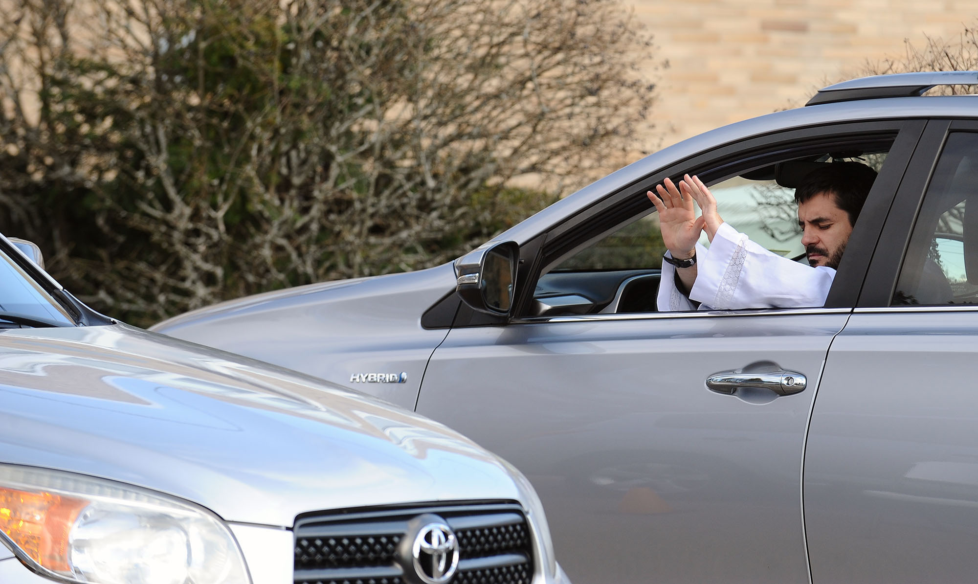 3/24/20-- MARLBOROUGH- Father Steven Clemance, pastor at the Immaculate Conception Catholic Church, offers a blessing at a drive-thru confession Thursday afternoon. Two priests offer to hear confession Tuesday and Thursdays from 4-6 p.m. [Daily News and Wicked Local Staff Photo/Art Illman]