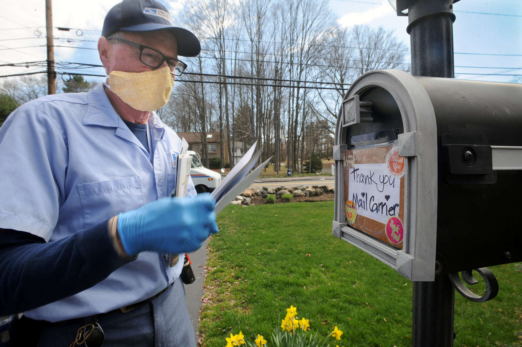 4/14/20-- FRAMINGHAM--  Letter carrier Brad Cauchon approaches a mailbox with a message on Winter Street Tuesday. [Daily News and Wicked Local Staff Photo/Art Illman]